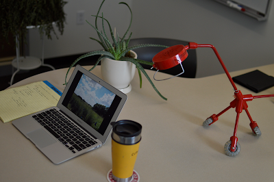 Laptop on desk with coffee, lamp, and plant