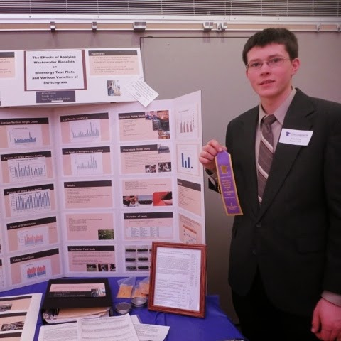 Brian Prchal posing with ribbon next to poster display