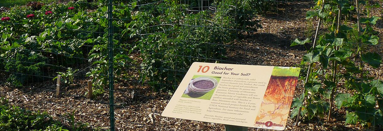 Sign about Biochar in front of fenced garden
