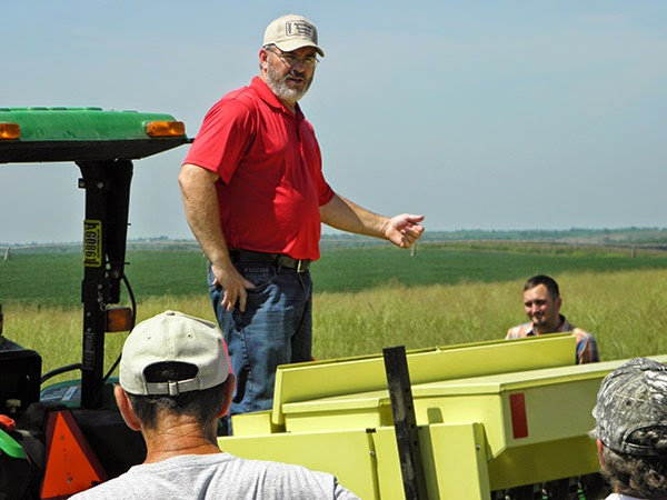 Rob Mitchell standing and speaking to others from tractor