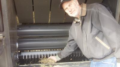 Kevin Shinners holding grasses near machinery