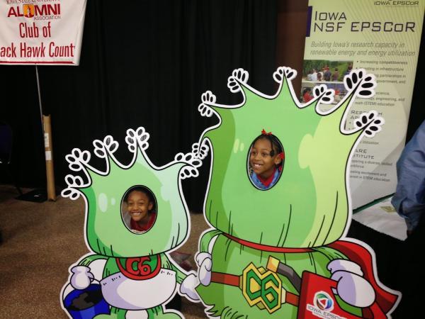 Children posing in face cutout of a biorenewables themed superhero