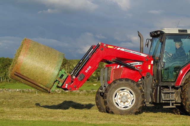 Farm machinery with hay bale on the end of mechanical arm